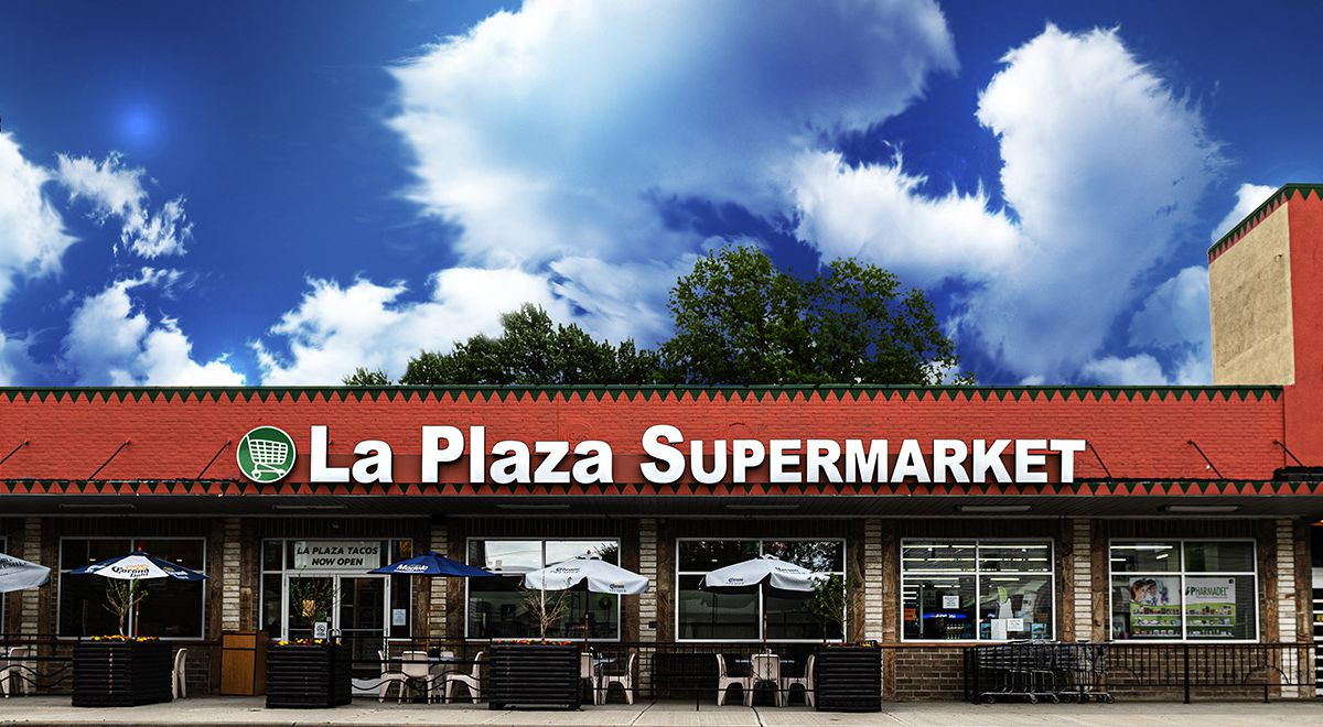 A grocery store exterior beneath a blue sky dotted with dreamy clouds
