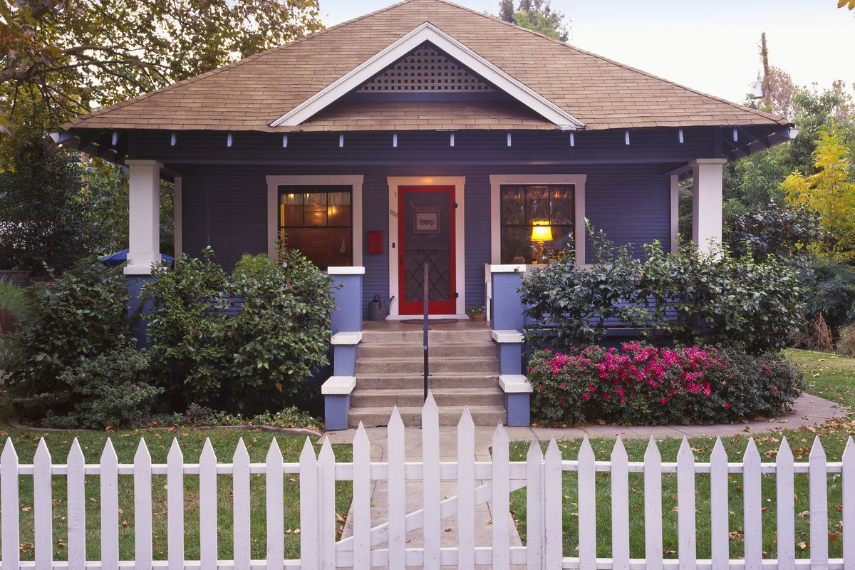 A vintage bungalow with a centered gable roof in front and  large covered front porch. A sidewalk and steps lead to the front door. There are tended-to shrubs and other plants around the house's perimeter and a large tree on the side.
