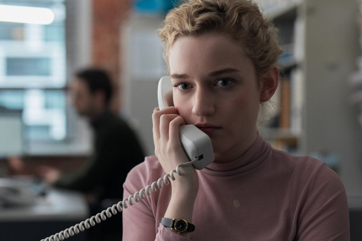 A young woman on the phone in a busy office.
