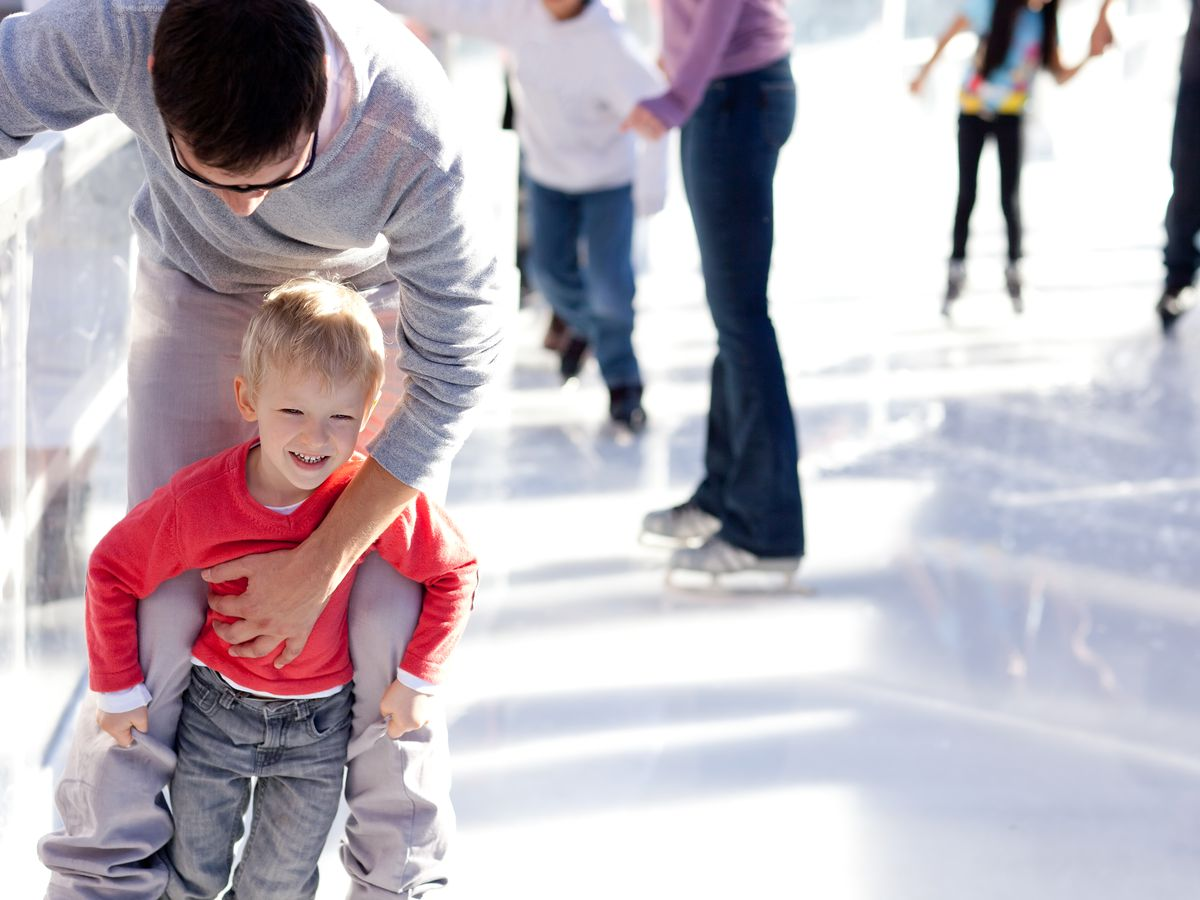 A child and an adult are ice-skating at a rink.