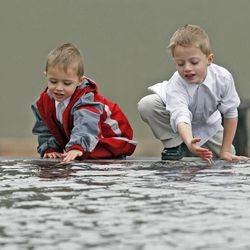 Michael DeGraw, left, and Ryan DeGraw enjoy the pond outside during The Church of Jesus Christ of Latter-day Saints' Saturday afternoon session of the 183rd Annual General Conference Saturday, April 6, 2013, in Salt Lake City.