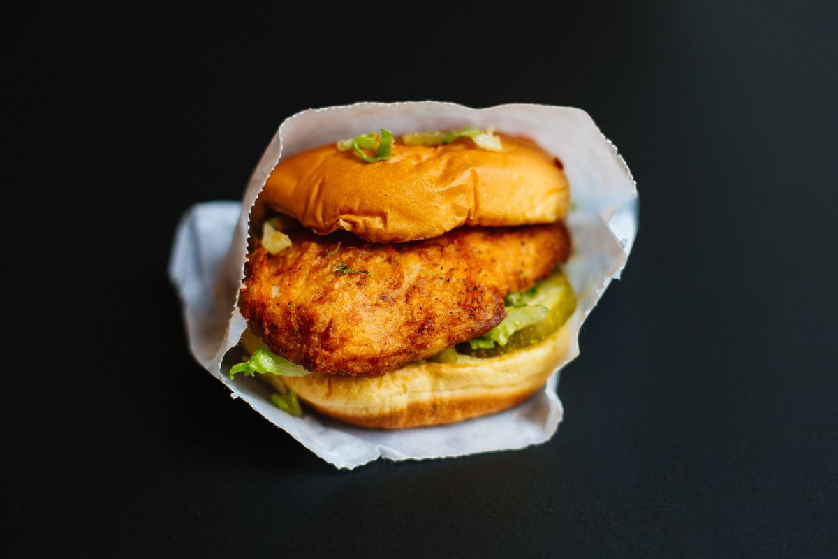 A fried chicken sandwich with lettuce and jam in a white package.