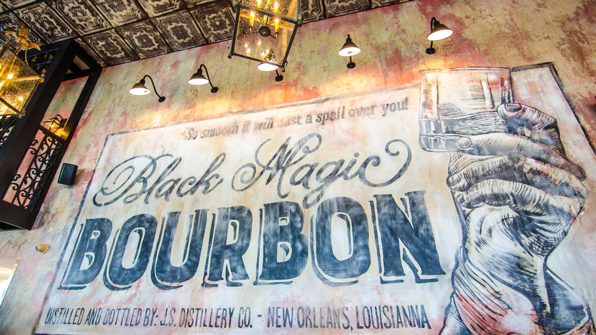 A restaurant wall is painted with shades of pink and orange, with an aged look. A giant black stenciled mural looks like a label for Black Magic Bourbon, with a hand holding up a glass.