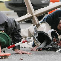 Investigators take a close look at the tail rotor section of the crashed helicopter. Emergency crews respond Tuesday, Dec. 2, 2014, to a helicopter crash in North Salt Lake.