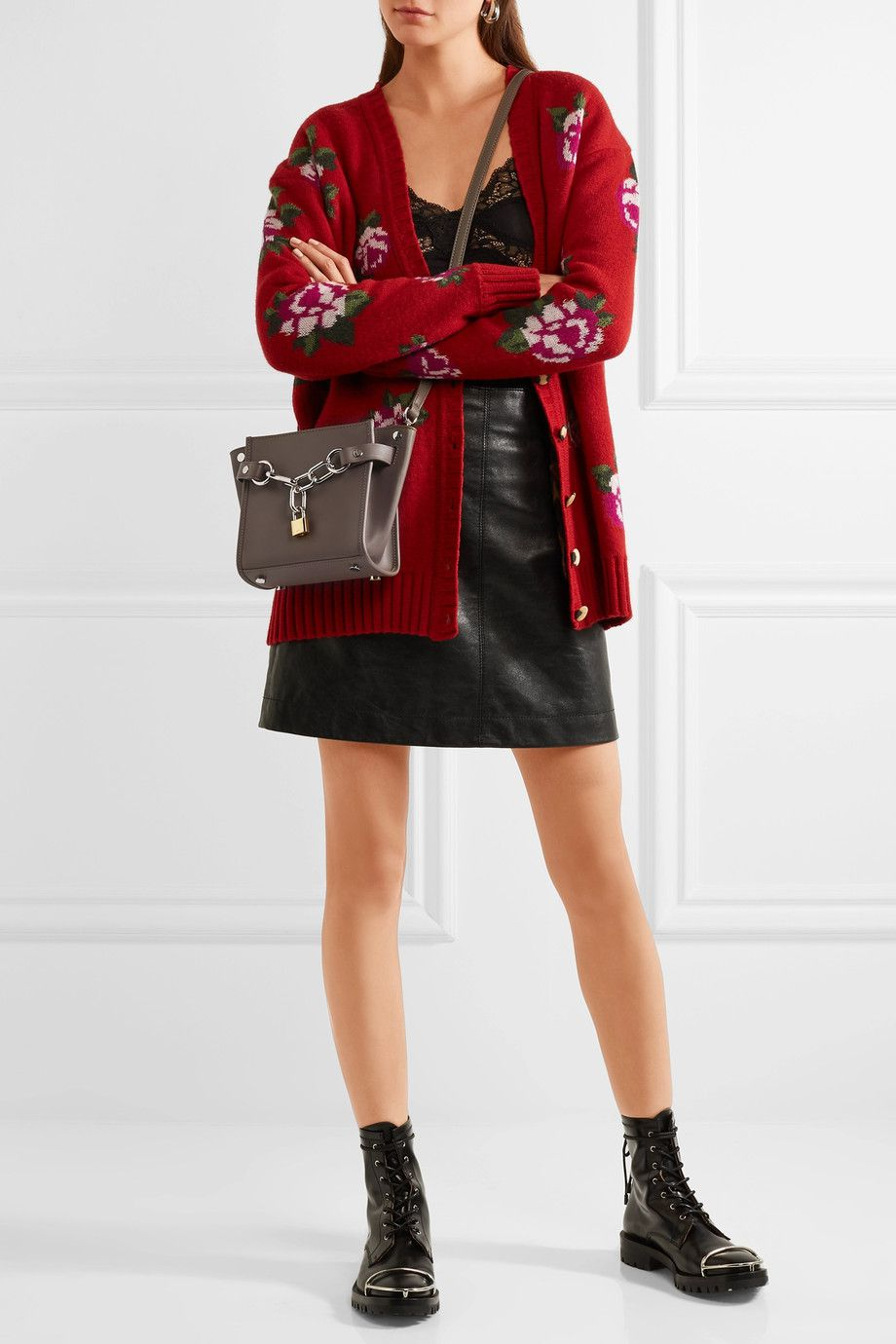 A model wearing a red jacket, black skirt, and holding a gray bag