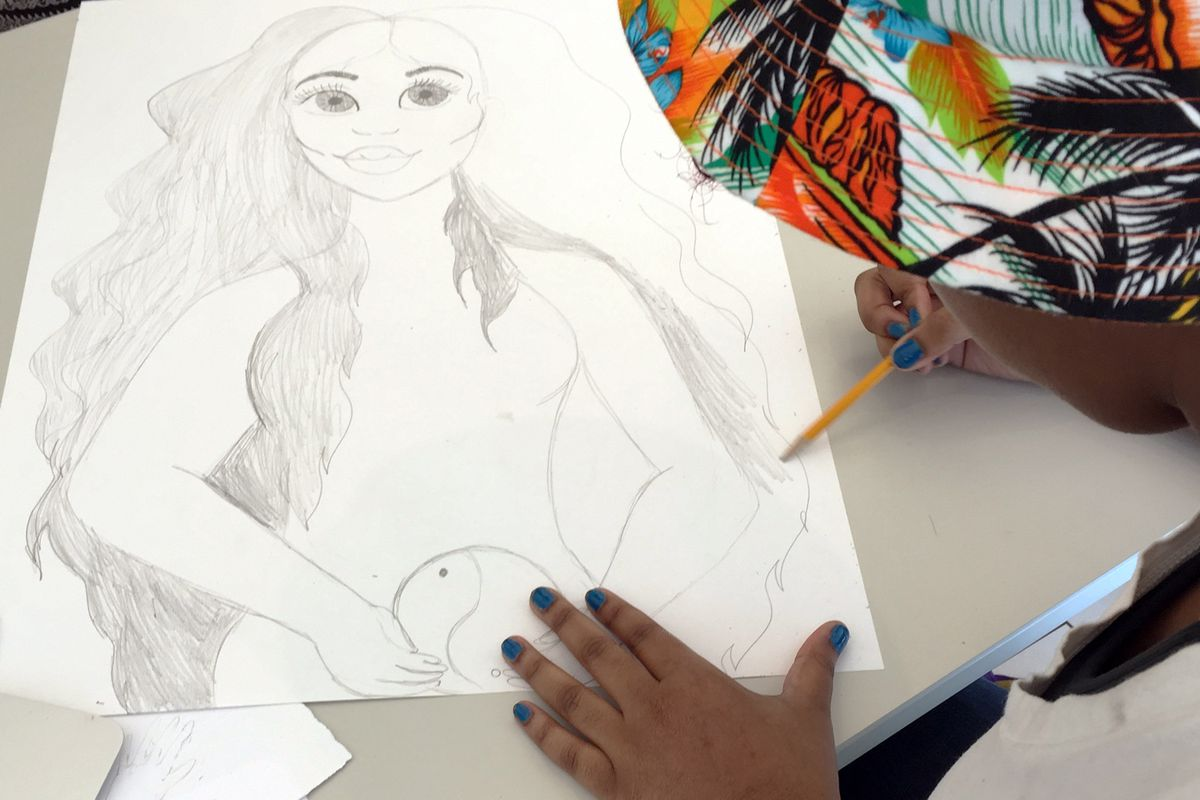 Student drawing a portrait of a woman with long hair.
