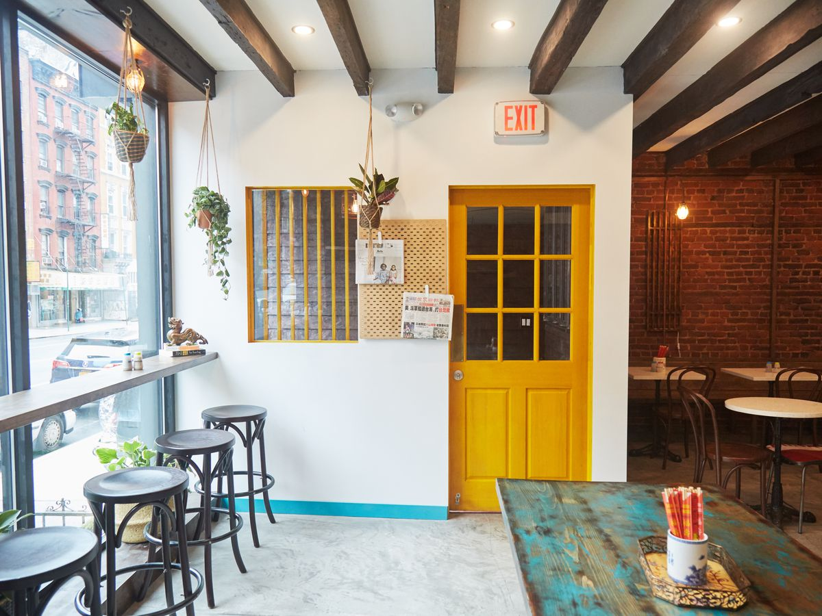 Potted plants hang from the ceiling in a naturally lit dining room with bar stools, high-top counters, and exposed brick