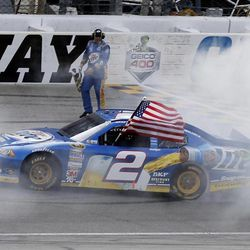 Brad Keselowski does a burnout as a crew member holds the checkered flag after winning the NASCAR Sprint Cup Series auto race at Chicagoland Speedway in Joliet, Ill., Sunday, Sept. 16, 2012.