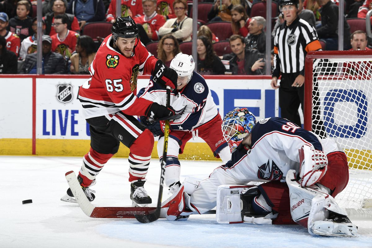 Andrew Shaw of the Chicago Blackhawks attempts a shot on goalie Elvis Merzlikins of the Columbus Blue Jackets