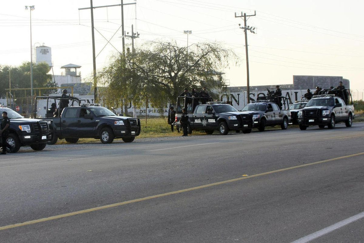 A group of Mexican federal police stand in front of the prison in Piedras Negras, Mexico, Monday Sept. 17, 2012. Authorities say 132 inmates have escaped from this jail in northern Mexico, sparking a search by federal police and soldiers in an area close