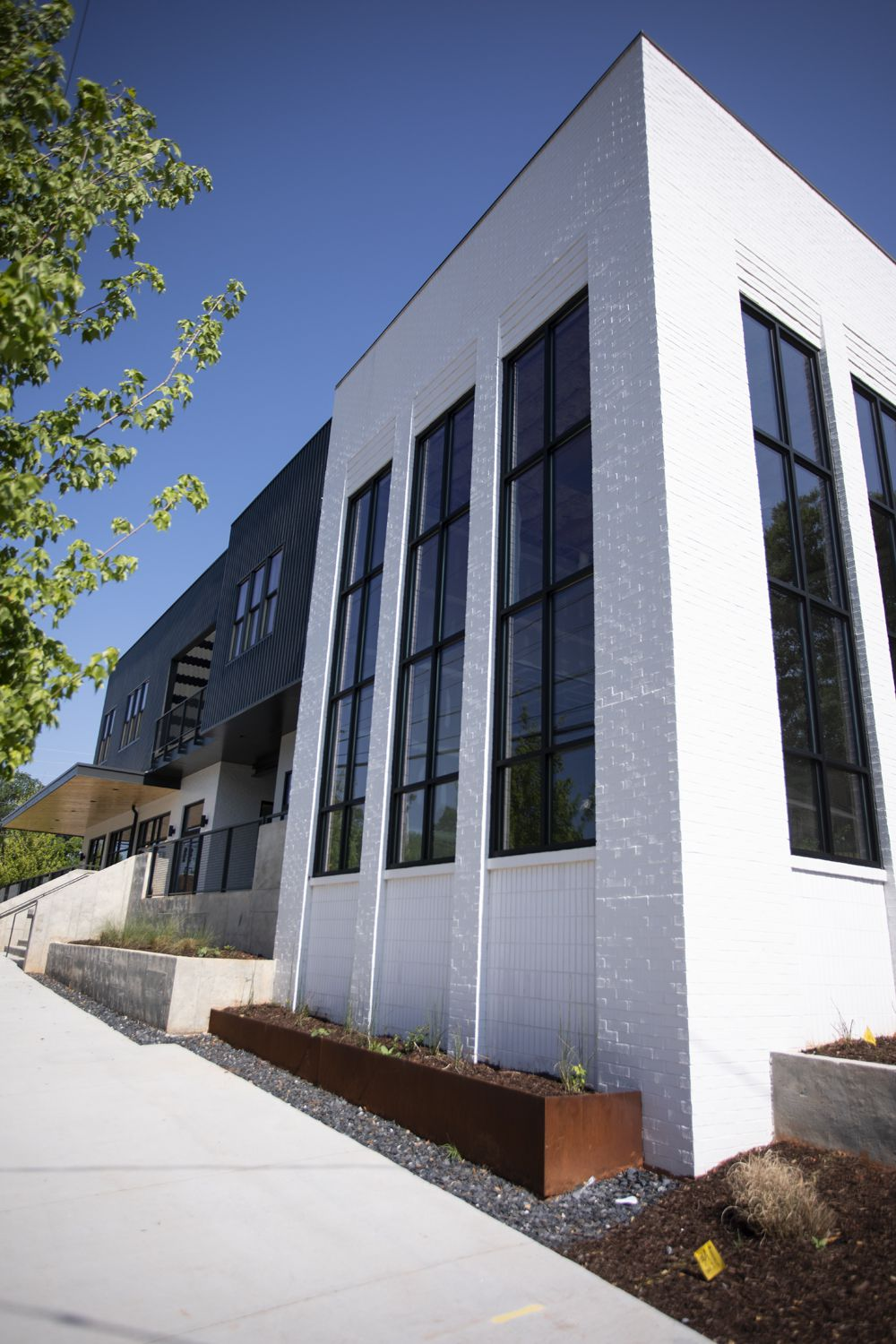 Another view of the office and retail building, featuring white brick and tall windows.
