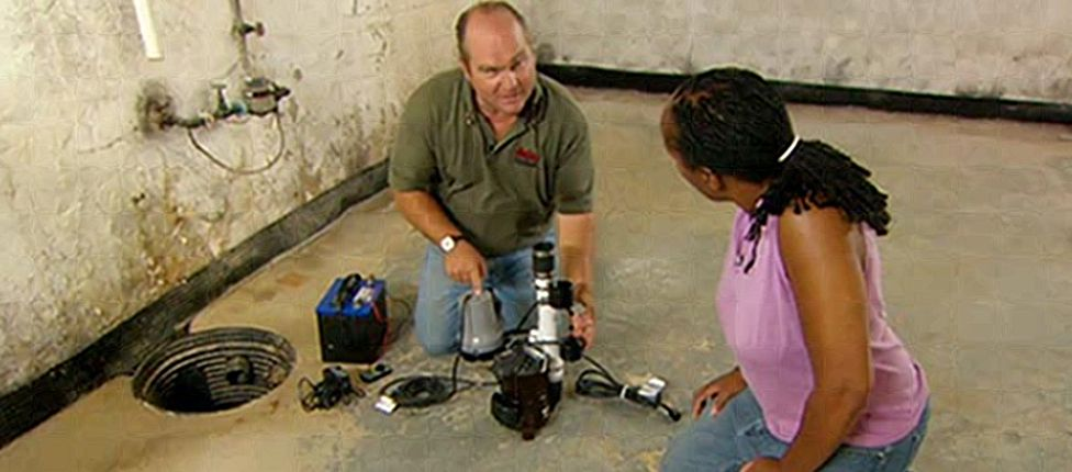 A professional showing a homeowner how to install a sump pump in the basement.