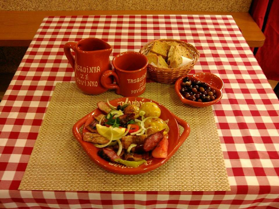 A decorated dish with meat and potatoes, with a basket of bread and a bowl of olives, along with a mug and pitcher on a checkered tablecloth