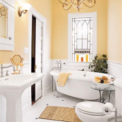 White freestanding tub in the middle of a yellow and white bathroom.