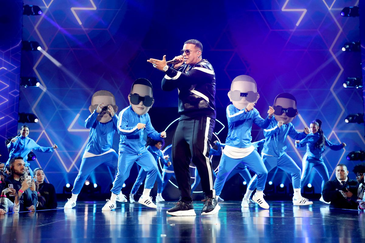Singer Daddy Yankee onstage with a microphone in front of dancers wearing Daddy Yankee masks and outfits.