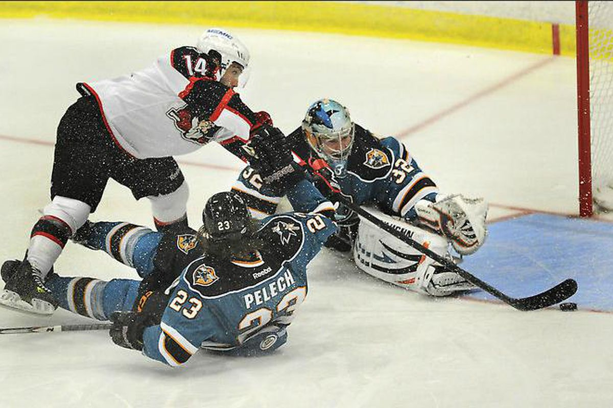 Chris Conner of the Portland Pirates slides a backhanded shot past Worcester Sharks goalie Alex Stalock early in the first period Friday night.