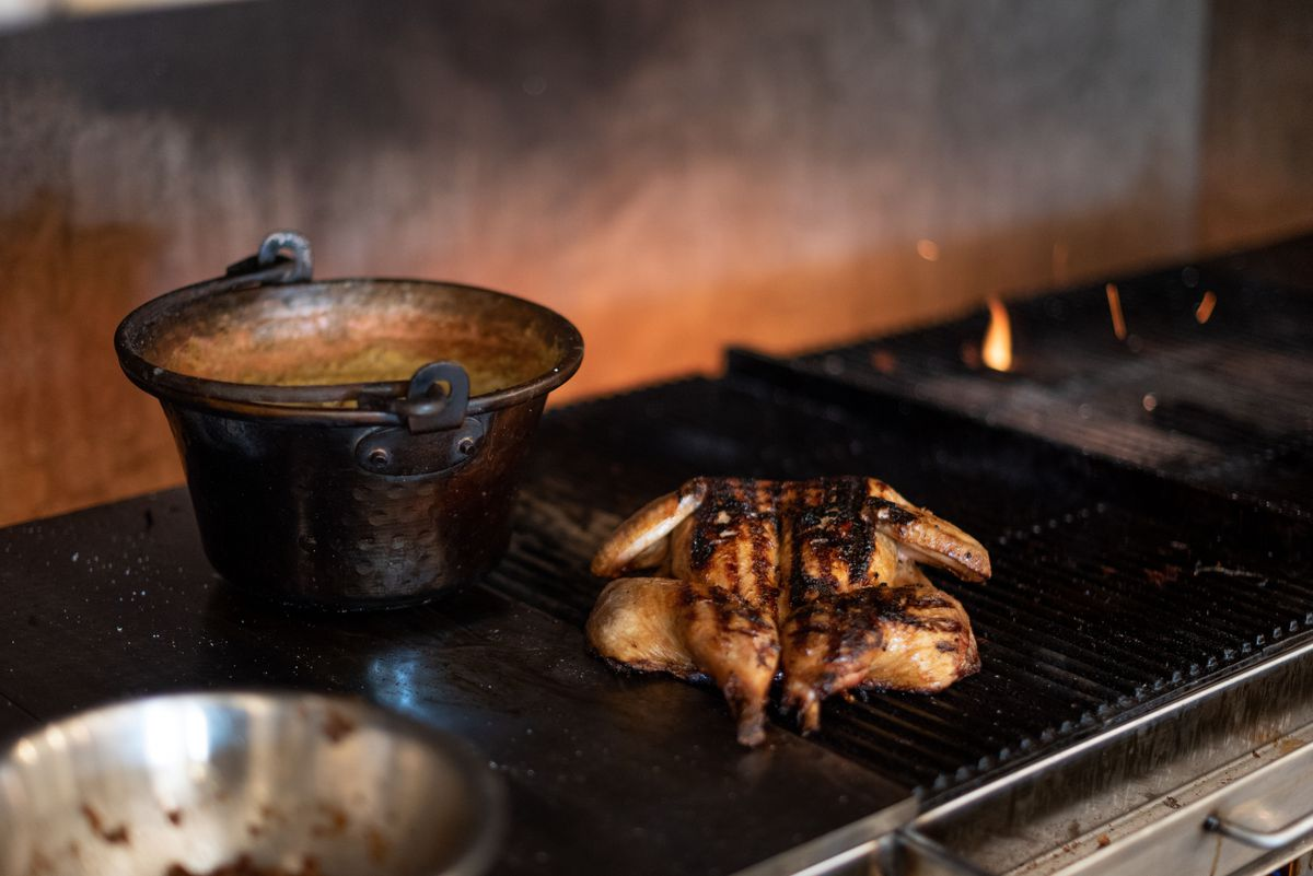 Chicken, charred from the grill, sits ready for service in a kitchen.