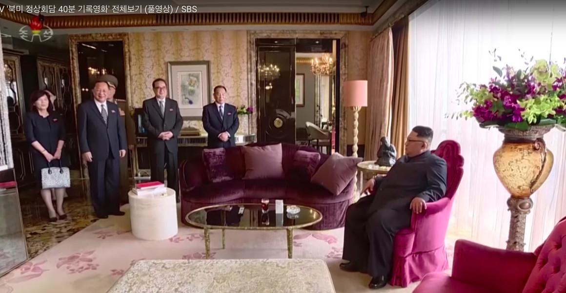 Kim Jong Un lounges in a hot pink velvet armchair.
