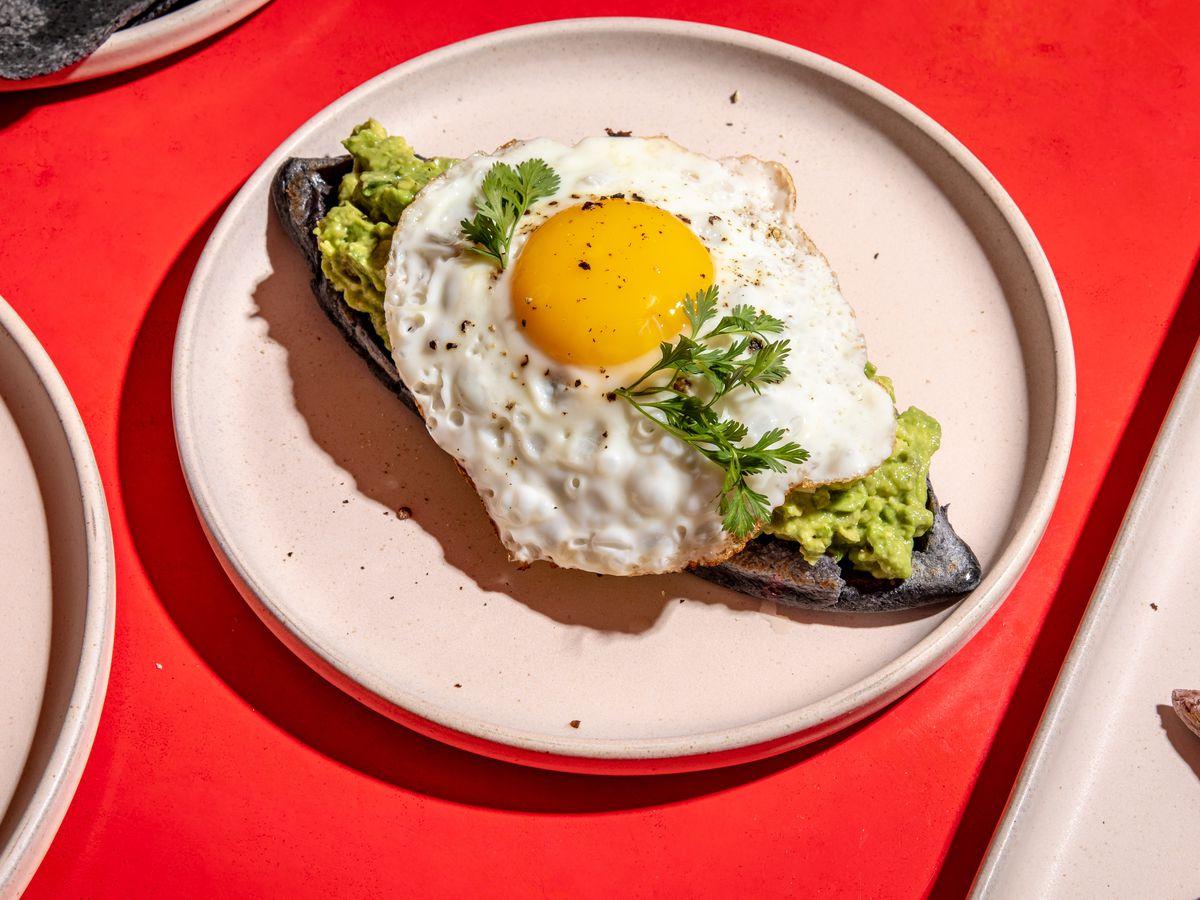 Sunnyside up egg sits atop an avocado memela on a white plate