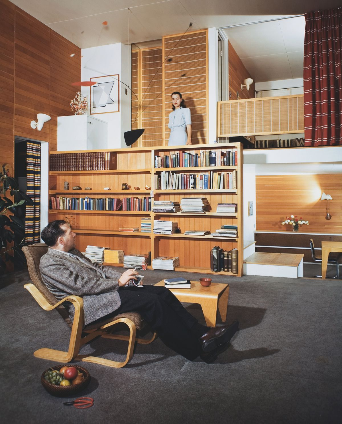 A man sits in a living room chair looking up at a woman standing on a mezzanine. The walls are lined with built-in wood bookshelves and the carpet is gray.