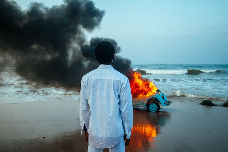 The Burial of Kojo: A Ghanian man stands in front of a burning Volkswagen beetle