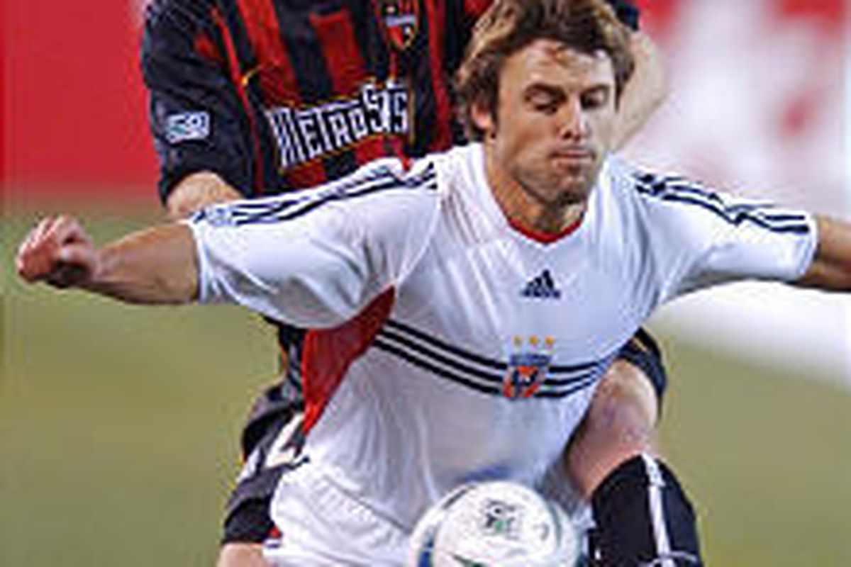 United midfielder Dema Kovalenko shields the ball from MetroStars defender Tim Regan during the second half of Saturday's playoff game.