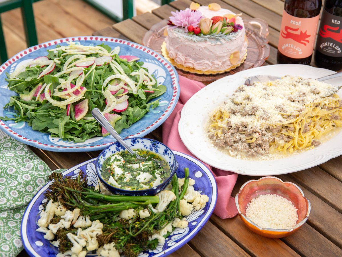 A slatted wooden table holds three plates: one with salad, one with parmesan-topped ragu pasta, and another with asparagus.