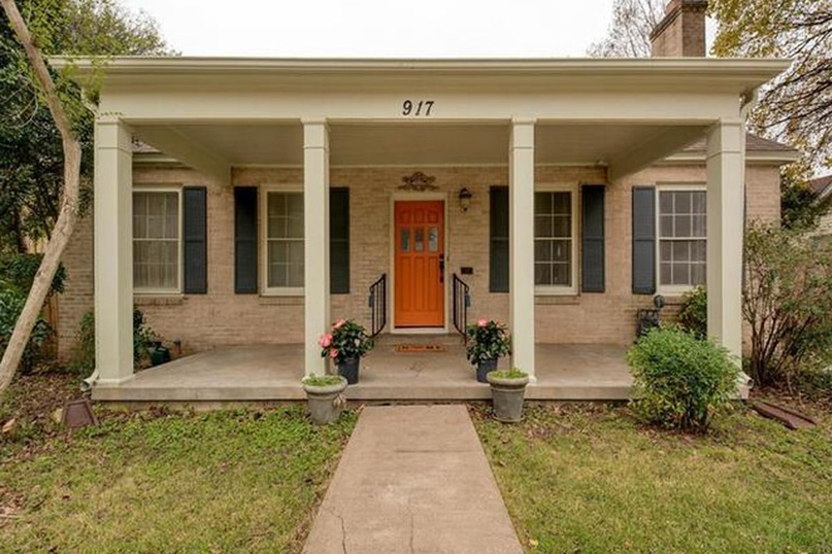 A light red brick one-story 1940 home with big concrete porch, white wooden columns, an inor railing to door, and red door, symmetrical windows on each side