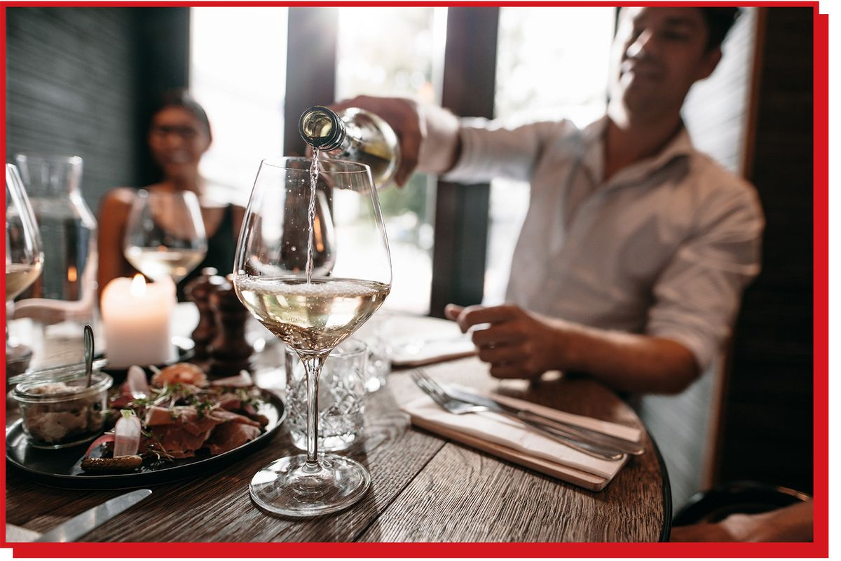 Man pours white wine into a glass at a restaurant table