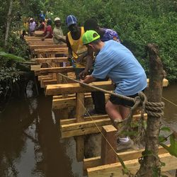 Members of the expedition group from Utah and some Ghanians help build a bridge between two villages thanks to Myan Moon's Eagle project.