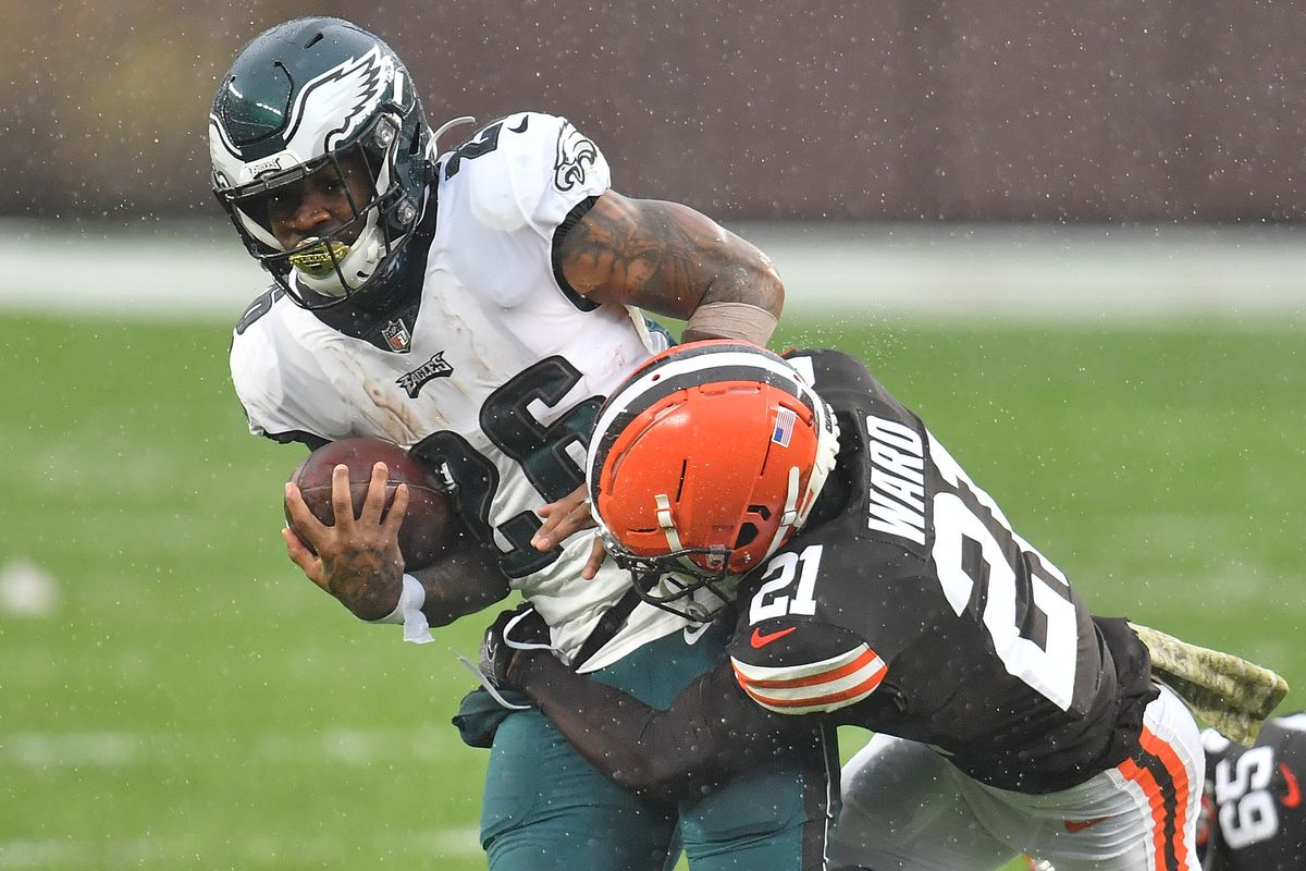 Miles Sanders #26 of the Philadelphia Eagles is brought down by Denzel Ward #21 of the Cleveland Browns during the first half at FirstEnergy Stadium on November 22, 2020 in Cleveland, Ohio.