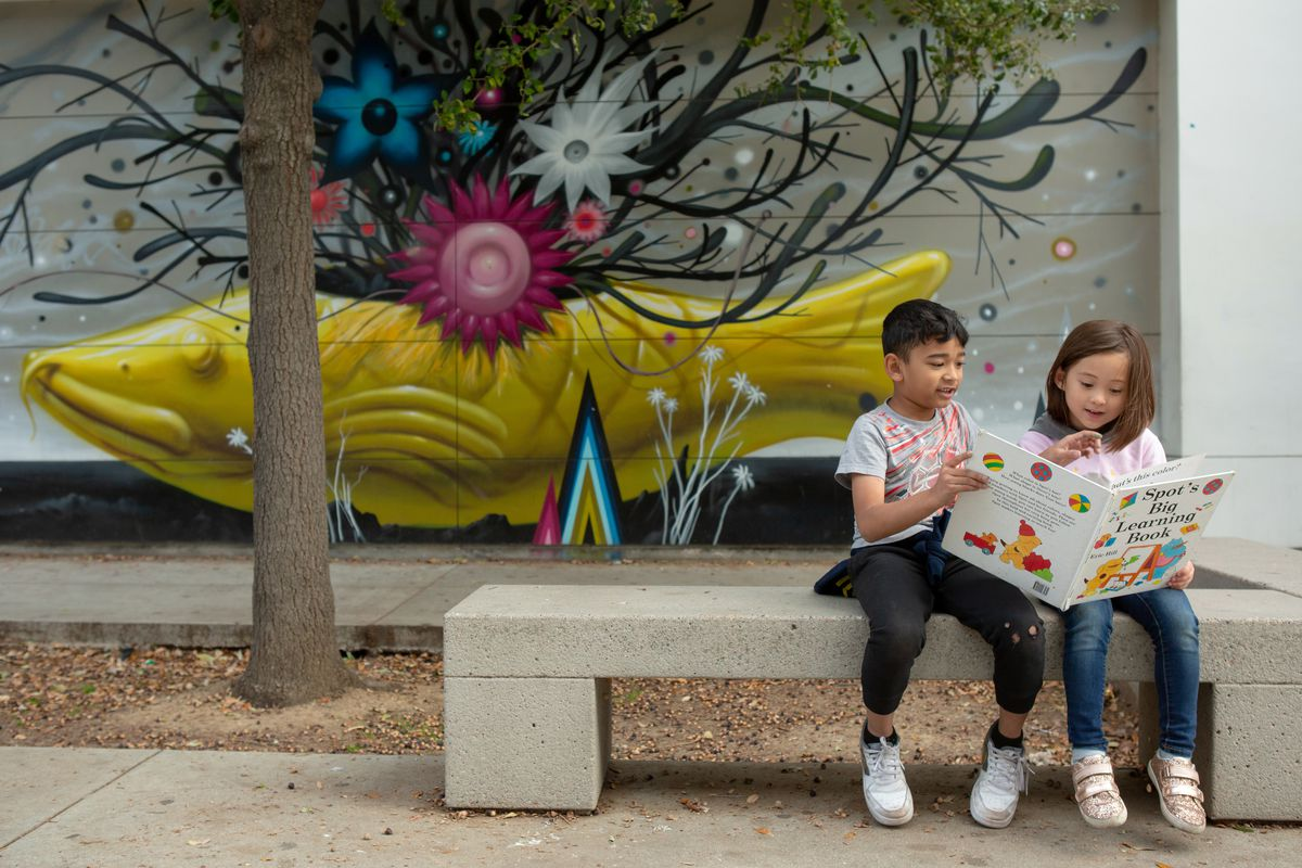 A boy and a girl share a picture book while sitting on a concrete bench in front of a concrete wall and a sculpture of a large yellow fish with a tangle of dark seaweed growing up from its back with blue, magenta and white flowers interspersed.