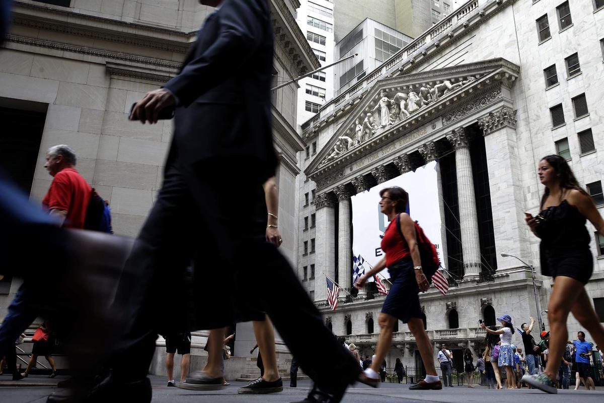FILE - In this Monday, Aug. 24, 2015, file photo, people walk past the New York Stock Exchange. The Republican tax plan eliminates a lot of exemptions and deductions, and applies the savings plus another $1.4 trillion over 10 years to lower rates. The ben