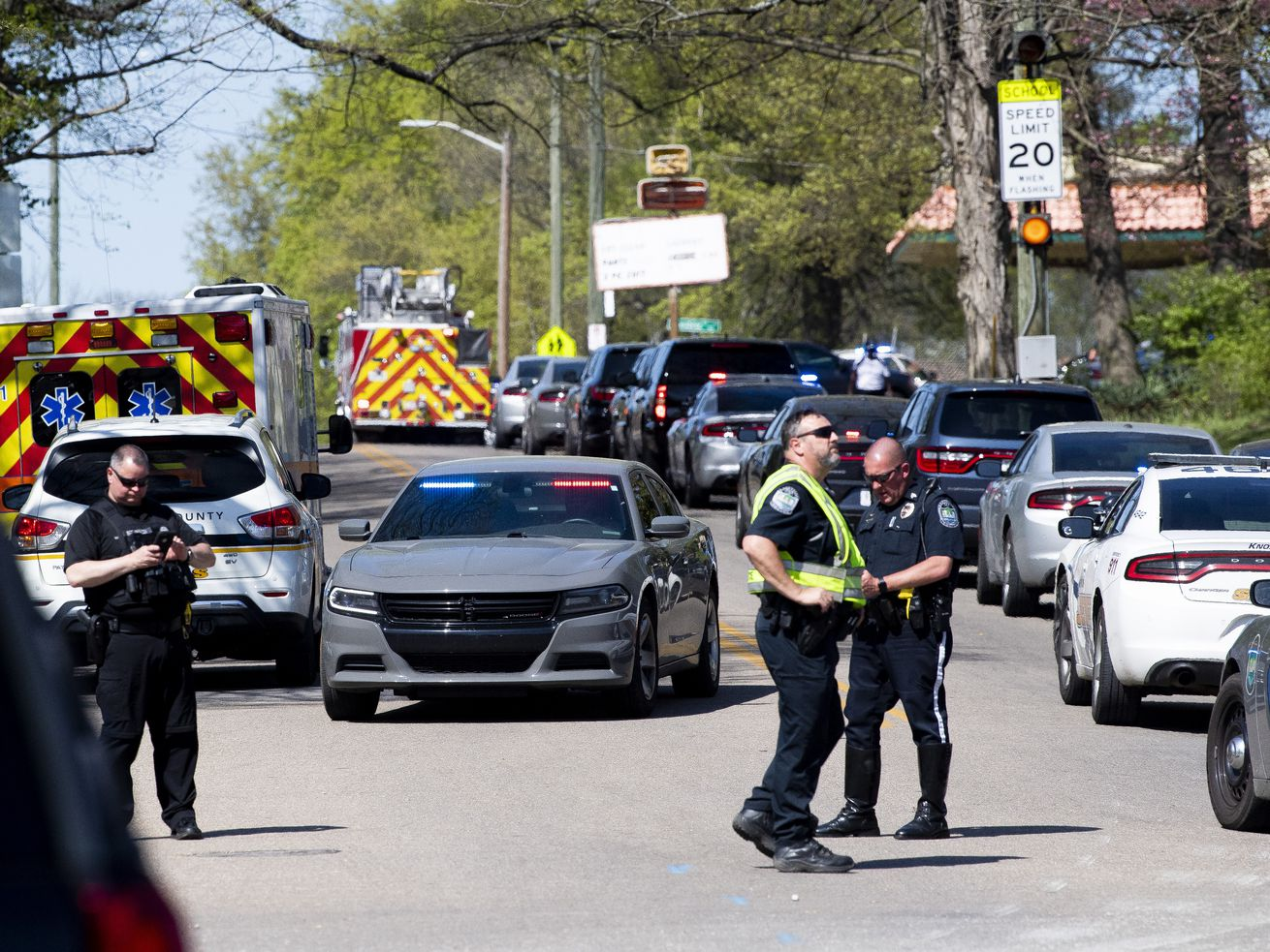 Police work in the area of Austin-East Magnet High School after a reported shooting Monday, April 12, 2021. Authorities say multiple people including a police officer have been shot at the school.