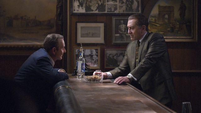 Pacino as Jimmy Hoffa and De Niro as Frank Sheeran across from each other at a bar.