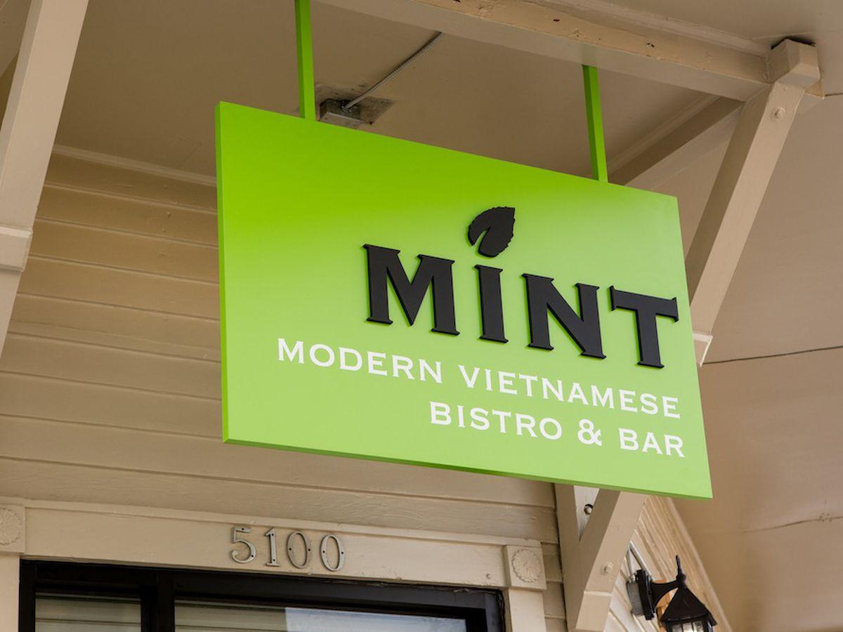 "A bright green sign hangs outside a restaurant reading ""Mint Modern Vietnamese Bistro & Bar"""