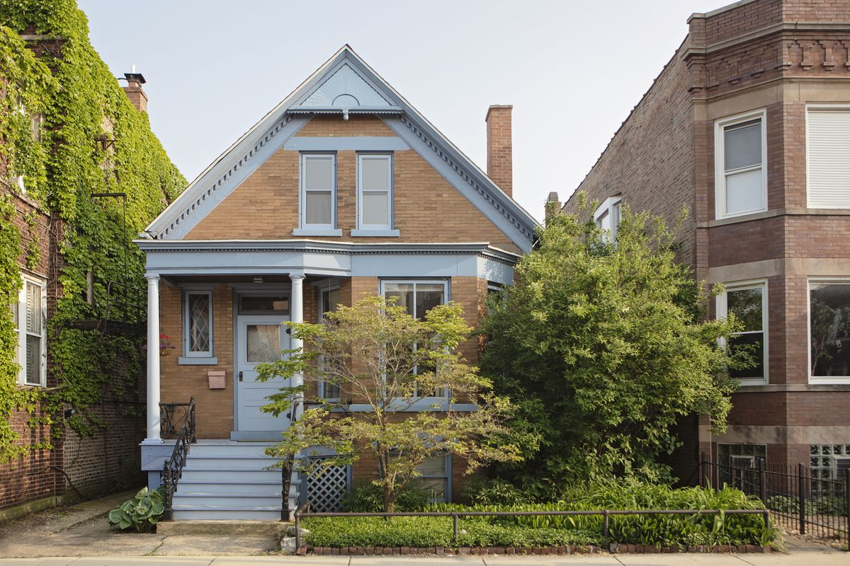 A one-story brick home with light blue trim in a Chicago neighborhood.