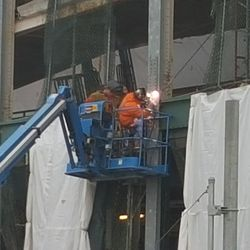 Close-up of workers in cherry-picker -