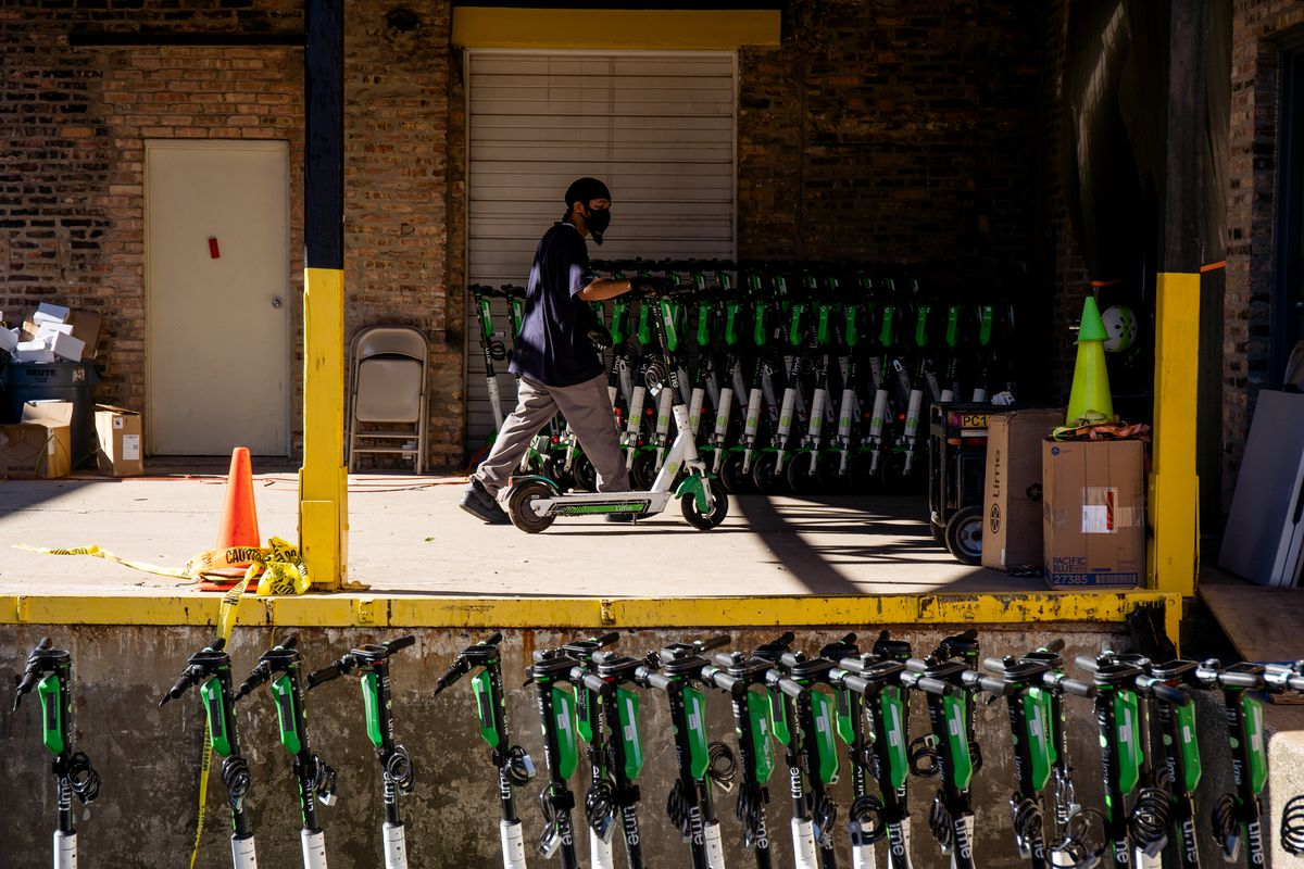 A worker wheels a Lime scooter into a warehouse in West Town Wednesday morning, Aug. 12, 2020. Lime deployed 1,000 scooters across Chicago Wednesday.