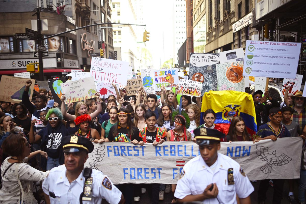 "Global Climate Strike protesters fill a New York City street with signs that read, ""Your ignorance is our future,"" and, ""Forest rebellion now."""