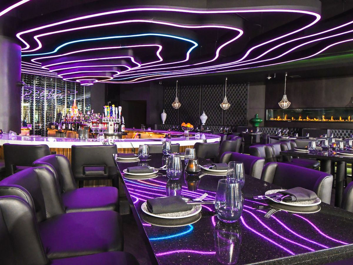 A purple lounge with neon on the ceiling
