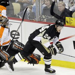 Pittsburgh Penguins' Matt Cooke (24) collides with Philadelphia Flyers goalie IIya Bryzgalov (30) during the first period of Game 5 of an opening-round NHL Stanley Cup hockey playoff series in Pittsburgh Friday, April 20, 2012.