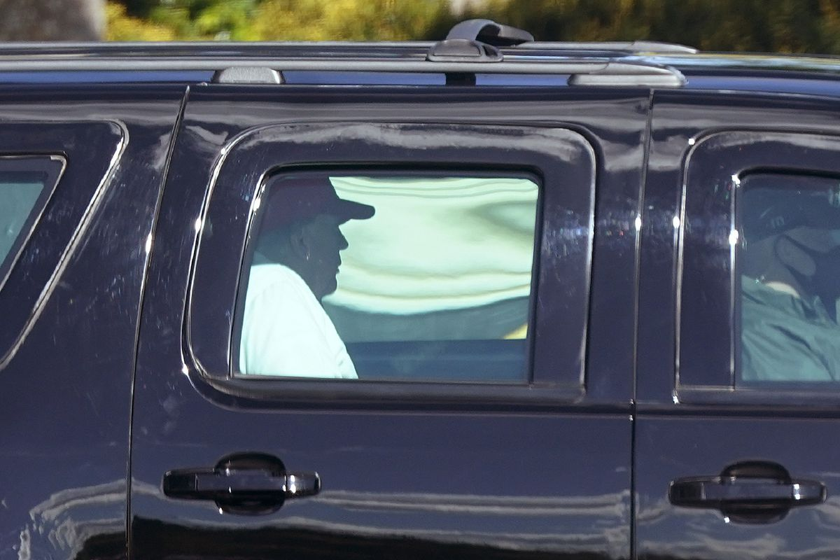 President Donald Trump rides in a motorcade vehicle as he departs Trump International Golf Club, Sunday in West Palm Beach, Fla.