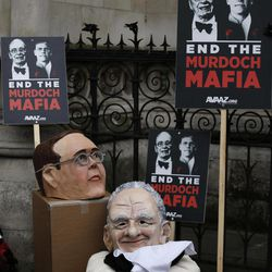 """Masks depicting Rupert Murdoch, bottom, and his son James rest alongside placards outside the Leveson inquiry at the High Court in London, after being taken off by protesters, Tuesday, Apr. 24, 2012.  James Murdoch defended his record at the head of his father's British scandal-tarred newspaper arm, saying Tuesday that he had been given assurances by subordinates """"which proved to be wrong.""""  Murdoch was testifying at Lord Justice Brian Leveson's inquiry into media ethics to answer questions about his role in the phone hacking scandal at Rupert Murdoch's now-defunct News of the World tabloid."""