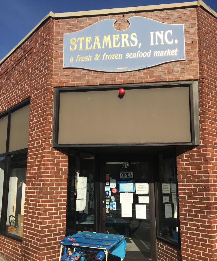 """A brick storefront with a folding table placed outside. Old-fashioned pale blue signage reads """"Steamers, Inc."""""""