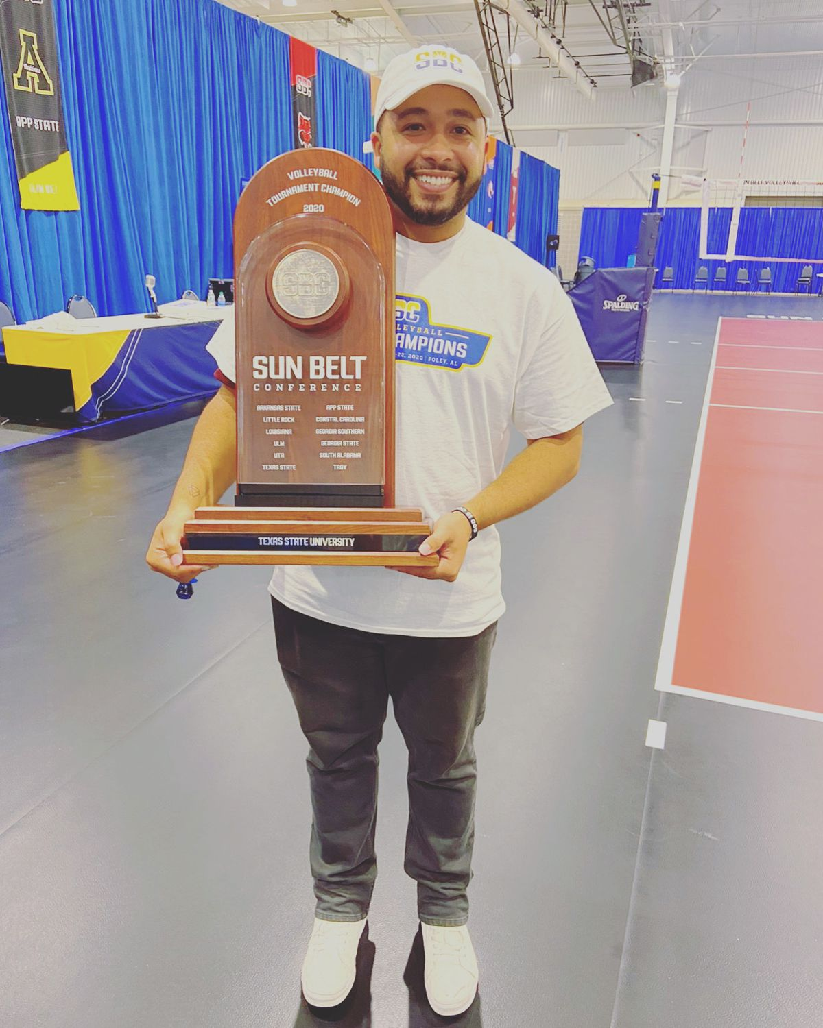 Keith Anderson with the Sun Belt trophy won by the Texas State volleyball team.