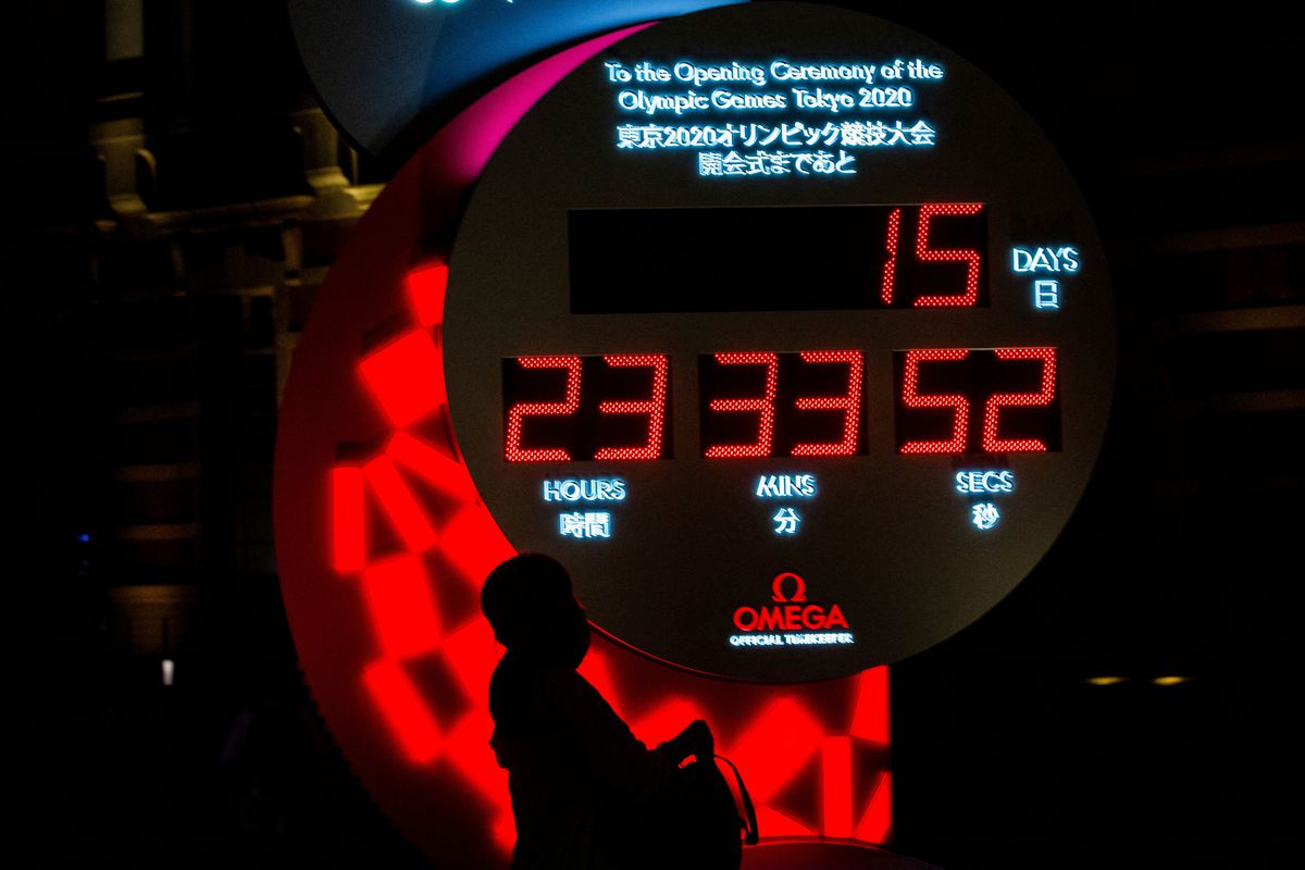 A passer-by walks past the countdown clock for the Tokyo 2020 Olympic Games displaying 15 days and 23 hours to go to the opening ceremony, outside Tokyo station in Tokyo on July 7, 2021.