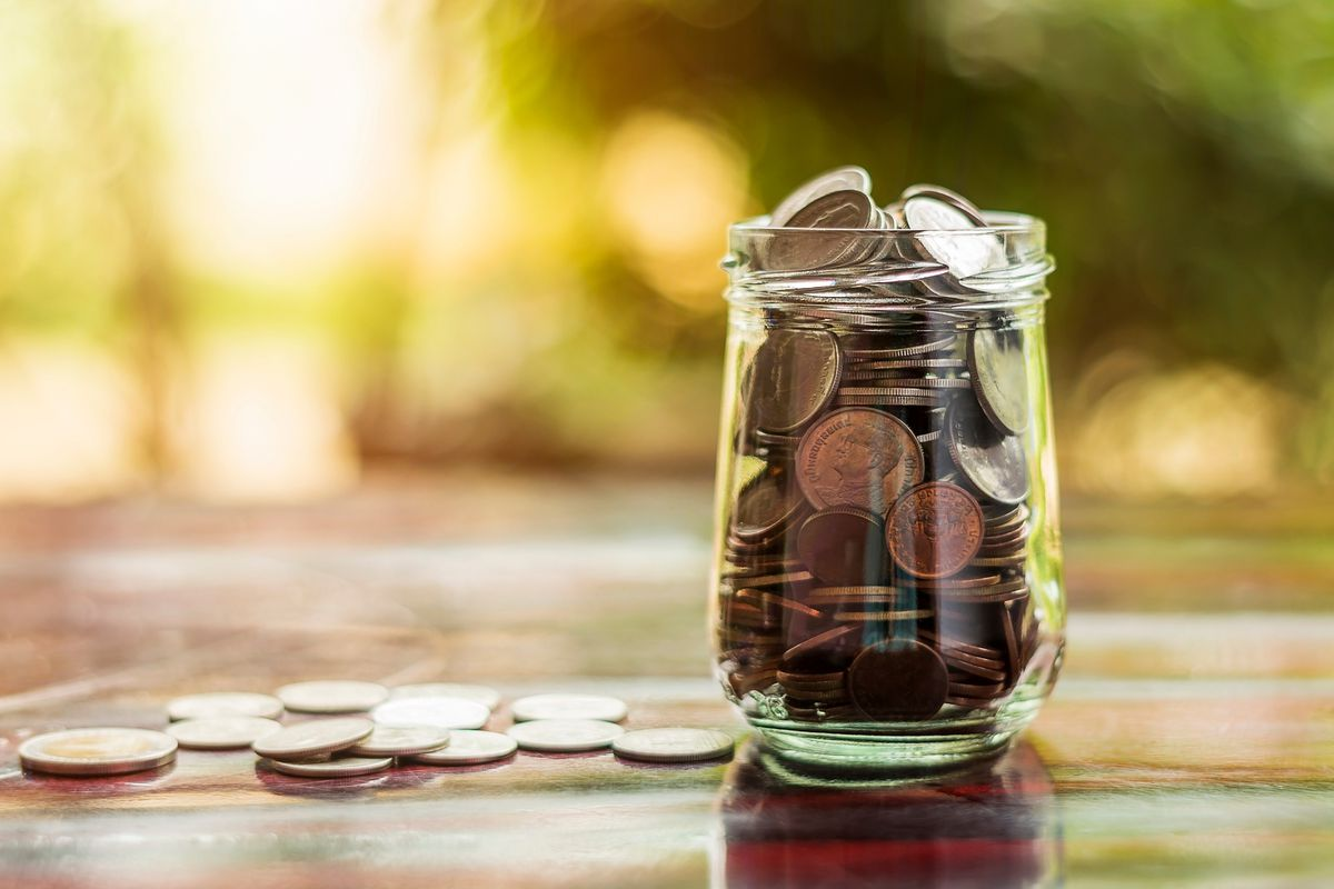 A glass jar full of coins, with more coins on the table beside it.