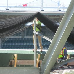 2:04 p.m. Protective netting being secured in the right-field bleachers -