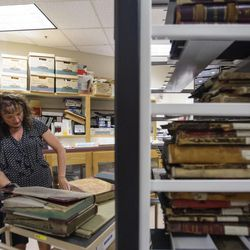Julie Dole, Salt Lake County chief deputy recorder, shows examples of old books inside the vault of the Salt Lake County Recorder's Office in Salt Lake City, Monday, June 5, 2017.